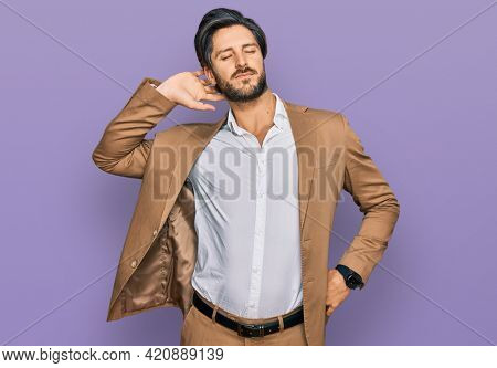 Young hispanic man wearing business clothes suffering of neck ache injury, touching neck with hand, muscular pain