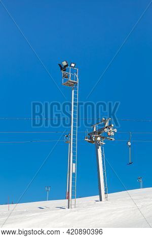 Ski Resort, Gentle Snow Slope With Artificial Lighting Towers And A Ski Lift. Mountain Slope For Ski