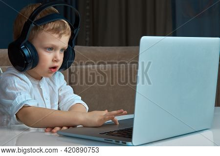 A Child With Blue Eyes Wearing Headphones Sits At A Desk And Uses A Touchpad To Control A Laptop