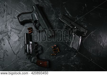 Top View Of Pistols And Bullets On Black Concrete Table. Vintage Revolver With A Drum. 9mm Handgun.