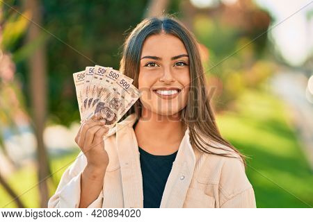 Young hispanic girl smiling happy holding mexican 500 pesos banknotes at the park.
