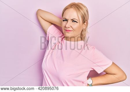 Young blonde woman wearing casual pink t shirt suffering of neck ache injury, touching neck with hand, muscular pain