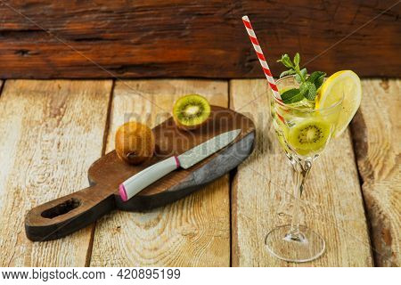 Cocktail With Kiwi Mint And Lemon In A Glass On A Wooden Table Next To Lemon And Kiwi On A Board.