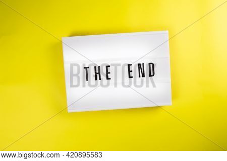 Lightbox With Message The End Isolated On Yellow Background. Concept Of Finish, Closure, End Of Year