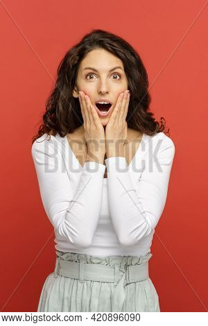 Surprised Young Woman With Open Mouth Holding Face In Palm Hands, Isolated Portrait Over Red Backgro