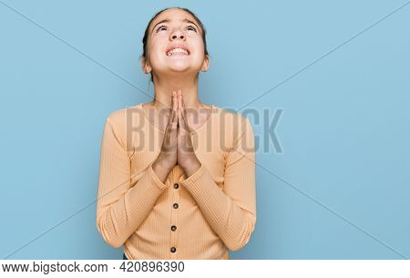 Beautiful brunette little girl wearing casual sweater begging and praying with hands together with hope expression on face very emotional and worried. begging.