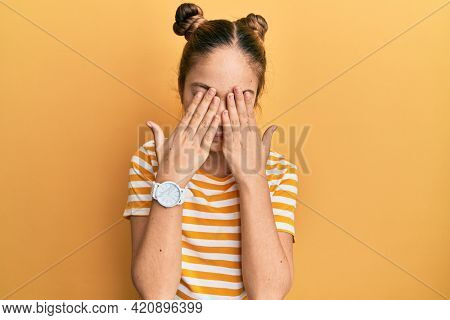 Beautiful brunette little girl wearing casual striped t shirt rubbing eyes for fatigue and headache, sleepy and tired expression. vision problem