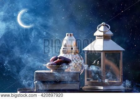 Ornamental Arabic lantern with dates and crescent moon glowing at night. Festive greeting card for Muslim holy month Ramadan Kareem.