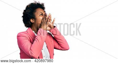 African american woman with afro hair wearing business jacket shouting angry out loud with hands over mouth