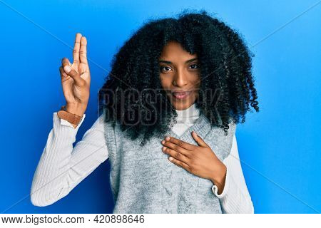 African american woman with afro hair wearing casual winter sweater smiling swearing with hand on chest and fingers up, making a loyalty promise oath