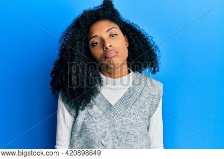African american woman with afro hair wearing casual winter sweater looking sleepy and tired, exhausted for fatigue and hangover, lazy eyes in the morning.