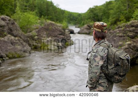 Hiker in camouflage clothing on the rocky shore of a mountain river. Russia. Primorskiy kray.