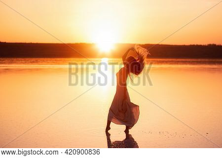 Silhouette Of A Slender, Graceful Girl In A Light, Satin Powdery Dress At Sunset. A Young Woman Walk
