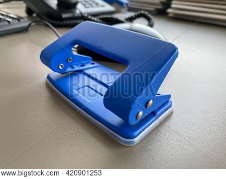 Blue Iron Metal Office Punch For Punching Holes In Sheets Of Paper And Documents On The Working Busi