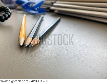Three Pencils Lie Sharply Sharpened Next To Folders With Sheets Of Paper And Documents On The Workin