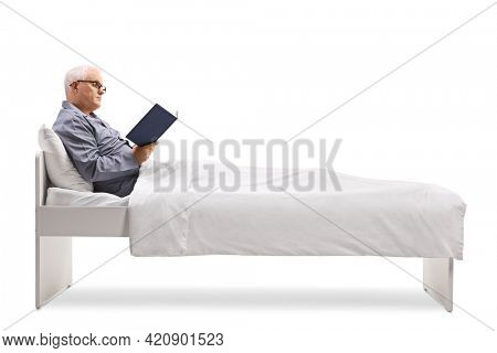 Mature man in pajamas sitting on a bed under duvet and reading a book isolated on white background