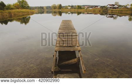Perspective View Of Wooden Pier At Lake. Damaged Empty Wooden Bridge Or Table Top With The Rural Lak