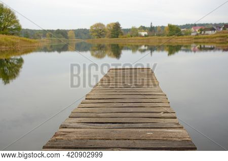 Perspective View Of Wooden Pier At Lake. Small Bridge In Water. Empty Wooden Bridge Or Table Top Wit