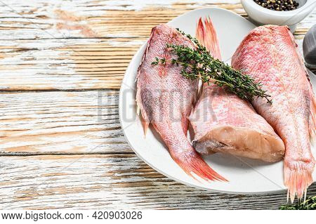 Whole Raw Red Perch Or Sea Bass Fish On A Plate. White Wooden Background. Top View. Copy Space