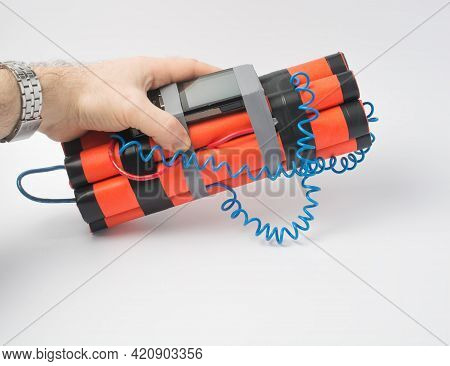 A Man Is Holding A Bomb With A Timer Made From A Smartphone. Survival And Terrorism Concept. White B