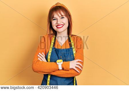 Redhead young woman dressmaker designer wearing atelier apron smiling with a happy and cool smile on face. showing teeth.