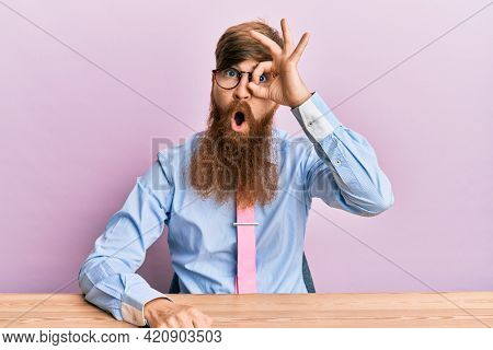 Young irish redhead man wearing business shirt and tie sitting on the table doing ok gesture shocked with surprised face, eye looking through fingers. unbelieving expression.