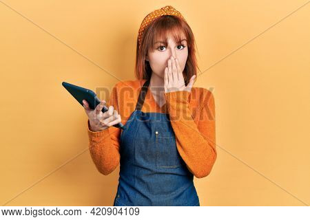 Redhead young woman wearing waitress apron holding touchpad device taking order covering mouth with hand, shocked and afraid for mistake. surprised expression