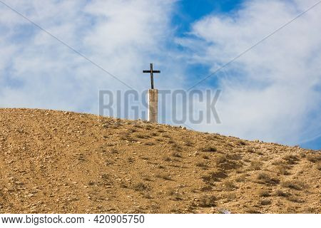 Christian Cross On The Blue Sky In The Mountains. Religious Cross In The Desert Of Israel. Sun And H