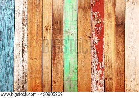 Texture of vintage wood boards with cracked paint of white, red, yellow, cyan and blue color. Horizontal retro background with old wooden planks of different colors