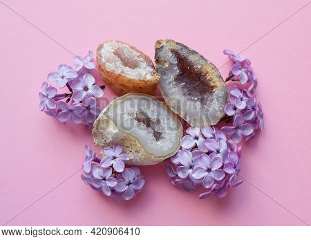 Beautiful Quartz Geodes With Lilac Flowers. Crystals Of Amethyst And Quartz On A Pink Background.