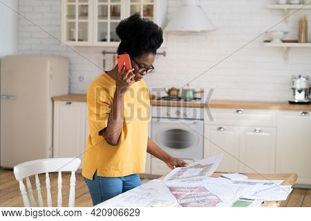 Serious Young Architect Discuss Project Blueprint On Phone Call. Female African Architectural Studen