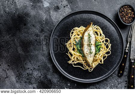 Spaghetti Pasta With Halibut Fish Steak And Spinach. Black Background. Top View. Copy Space