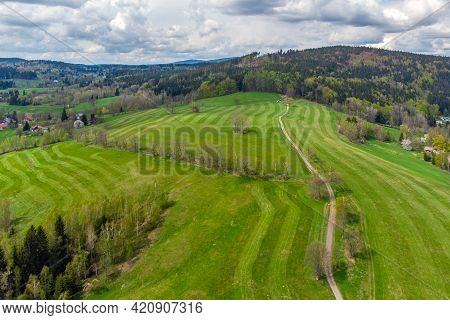 Lush Green Spring Hilly Landscape With Rural Fields And Road With Alley Of Trees