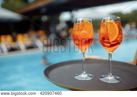 Glass Of Delicious Cocktail Near Swimming Pool, Space For Text. Refreshing Drink