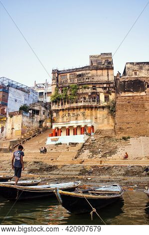 Varanasi, India - November 01, 2016: Boat And Boatman On Ganges River Bank Against Ghat With Old And