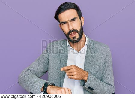 Young hispanic man wearing business clothes in hurry pointing to watch time, impatience, upset and angry for deadline delay