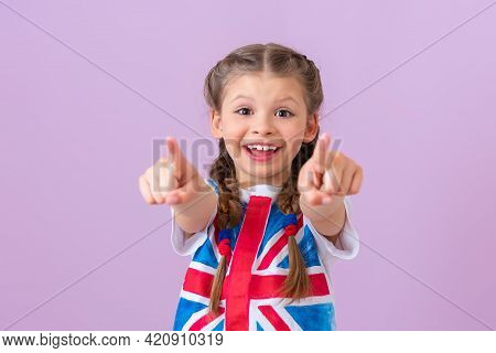 A Teenage Girl With An English Flag Points Her Fingers Forward.