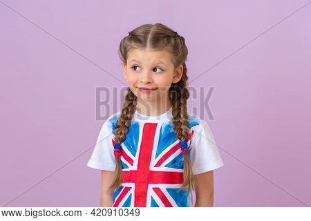 A Little Girl With An English Flag On Her T-shirt Looks Away.