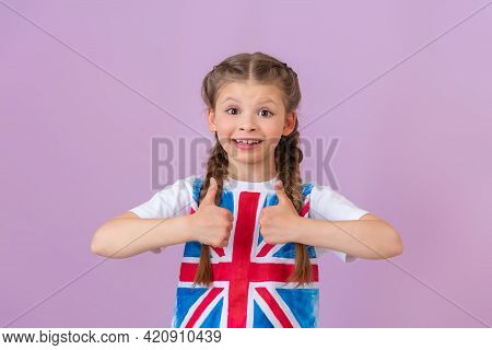 A Small, Beautiful Girl With Braids On An Isolated Background Gave A Thumbs-up. English Flag On The