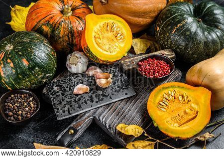 Food Composition With Pumpkins, Cleaver And Cutting Board. Black Background. Top View