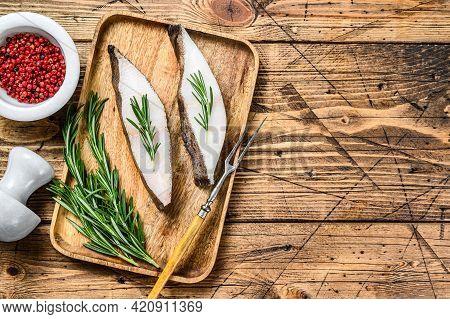 Raw Halibut Saltwater Fish Steak. Wooden Background. Top View. Copy Space
