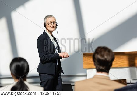 Mature Lecturer In Headset Looking At Participants On Blurred Foreground.