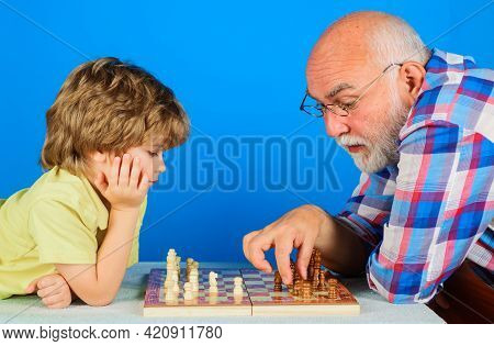 Grandson Playing Chess With Grandpa. Grandfather Teaching Grandchild Play Chess. Family Relationship