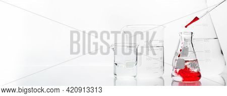Clear Glass Flask And Beaker With Orange Drop Solution In Chemistry Science Research Lab White Banne