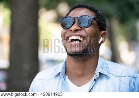 African American Man Smiling While Walking Outdoors.
