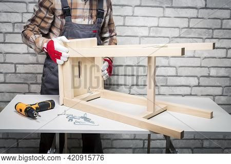 Man In Uniform Assembling Wooden Chair Furniture At Home. Assembly Furniture Service.