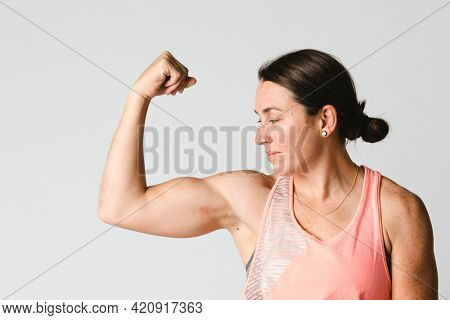 Female athlete flexing her arms