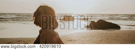 Woman strolling the beach at sunset