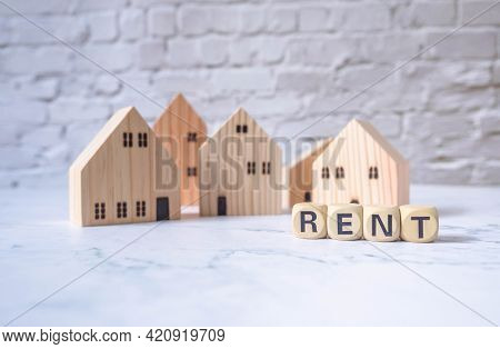 Miniature House And Wooden Blocks With The Word Rent On Marble Table.real Estate Concept.rent Apartm