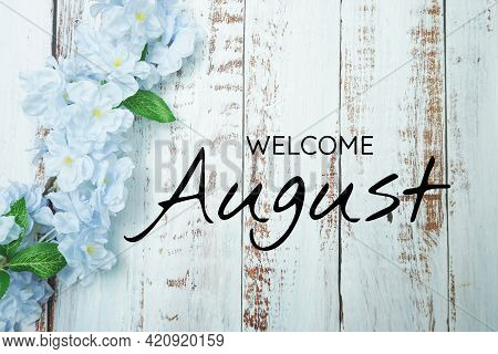 Welcome August Text And Blue Flower Decoration On Wooden Background